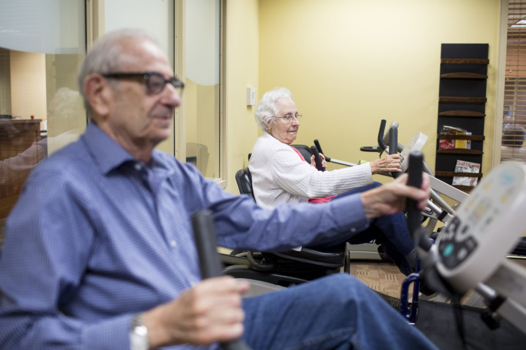 Sumner and Joyce Richman ride bikes together at the gym at Waverly Gardens in North Oaks, Minn., on Thursday, Oct. 1, 2015. Sumner tries to get Joyce down to bike at least 3 times a week for 10 minutes. (Jenn Ackerman for STAT) Photo by Ackerman + Gruber