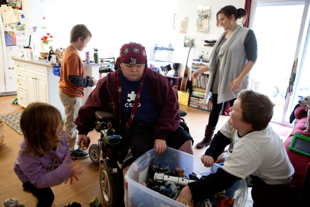 Norah McNary, 4, James McNary, 8, Austin Leclaire, 16, Jenn McNary, and Max Leclaire, 13, look through a box of toys in their apartment. Austin and Max have Duchenne muscular dystrophy, and are taking an experimental drug that has had a positive impact on their quality of life.