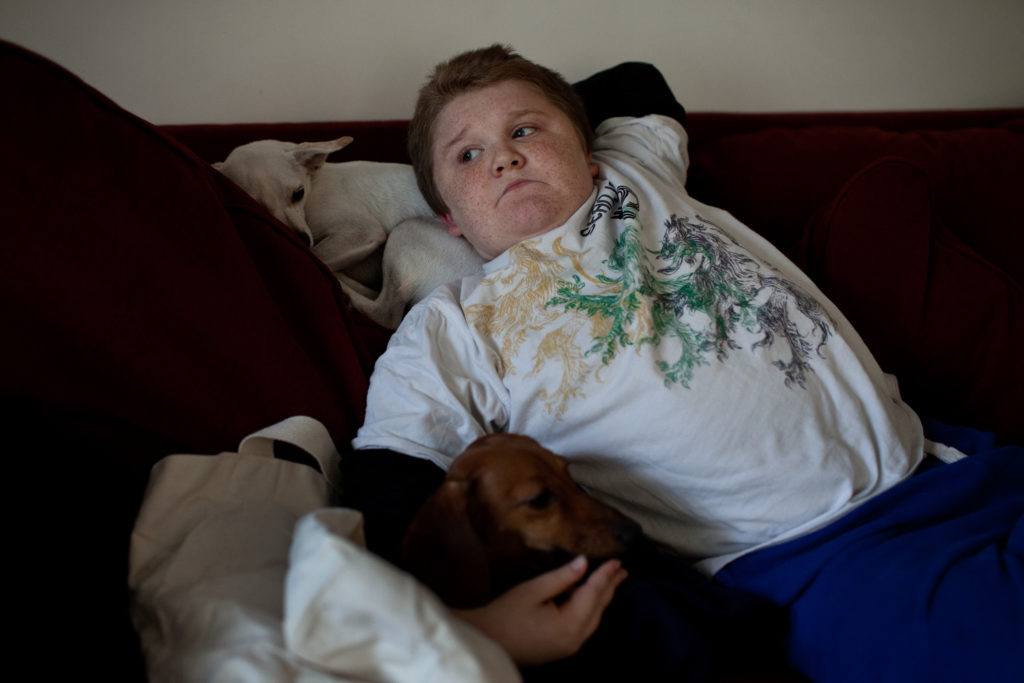 Max Leclaire, 13, relaxes at home in his apartment.