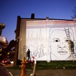 A mural of Freddie Gray is painted on the side of a building by local artist Nether, right, across the street from a makeshift memorial where Gray was arrested Sunday, May 3, 2015, in Baltimore. Baltimore's mayor has lifted a citywide curfew six days after riots were sparked over the death of a Gray who suffered a severe spinal injury while in police custody. (AP Photo/David Goldman)