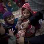 "An Afghan refugee child held by her elder sister receives a polio vaccine from a Pakistani health worker, on the outskirts of Islamabad, Pakistan, Wednesday, Feb. 26, 2014. Pakistan's beleaguered battle to eradicate polio is threatening a global, multi-billion dollar campaign to wipe out the disease worldwide. Because of Pakistan, the virus is spreading to countries that were previously polio free, say U.N officials. ""The largest poliovirus reservoir of the world,"" is in Peshawar, the capital of Pakistan's northwest Khyber Pukhtunkhwa province, which borders Afghanistan, according to the World Health Organization. (AP Photo/Muhammed Muheisen)"