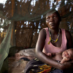A woman holds her baby under a mosquito net, meant to prevent malaria transmission, at a refugee camp in Yida, South Sudan.   ---  YIDA REFUGEE CAMP, SOUTH SUDAN - JULY 5: Rihab Kisa holds her newborn baby girl Jajia, born overnight inside her small hut at the Yida refugee camp along the border with North Sudan July 5, 2012 in Yida, South Sudan. The number of people arriving at the Yida refugee camp increases every day with the current population exceeding 64,000, as refugees continue to flee South Kordofan in North Sudan. Refugees arriving from the North can number between 500 to 1,000 a day and many have experienced long, arduous journeys without food to reach the camp. The rainy season has increased the numbers suffering from diarrhea, severe malnutrition and malaria. Even with refugees having food, there are sanitation issues causing increasing incidents of illness with the field hospitals saying that 95% of all patients are under the age of five. (Photo by Paula Bronstein/Getty Images)