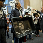 FILE - In this Thursday, Oct. 1, 2015, file photo, carrying an image of Turing Pharmaceuticals CEO Martin Shkreli in a makeshift cat litter pan, AIDS activists and others are asked to leave the lobby of 1177 6th Ave. in New York, during a protest highlighting pharmaceutical drug pricing. A Senate committee tasked with protecting seniors launched an investigation Wednesday, Nov. 4, 2015, into drug price hikes by Turing, Valeant Pharmaceuticals, Retrophin Inc. and Rodelis Therapeutics, responding to public anxiety over rising prices for critical medicines. (AP Photo/Craig Ruttle, File)