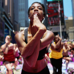 NEW YORK, NY - JUNE 21:  Aisha Johnson (C) and other enthusiasts perform yoga in Times Square during an event marking the summer solstice on June 21, 2013 in New York City. Thousands of yogis will attend the free day-long event in Manhattan on the longest day of the year.  (Photo by Mario Tama/Getty Images)