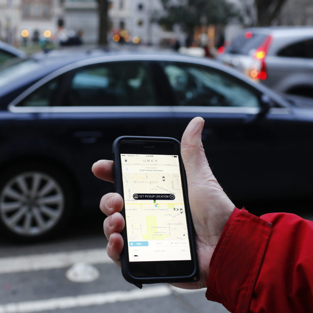 An UBER application is shown as cars drive by.