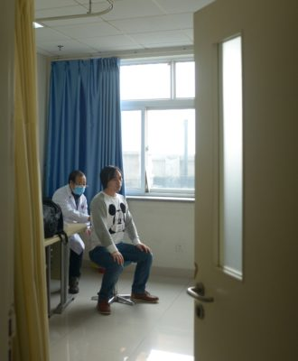 A doctor treats a patient at Wang Fu Hospital in Beijing.