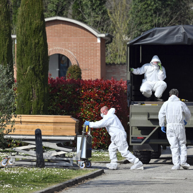 A convoy of Italian Army trucks is unloaded upon arrival from Bergamo carrying bodies of coronavirus victims to the cemetery of Ferrara, Italy, where they will be cremated, Saturday, March 21, 2020.