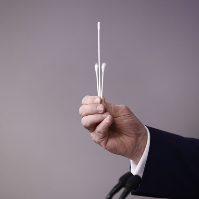 Donald Trump holding swabs