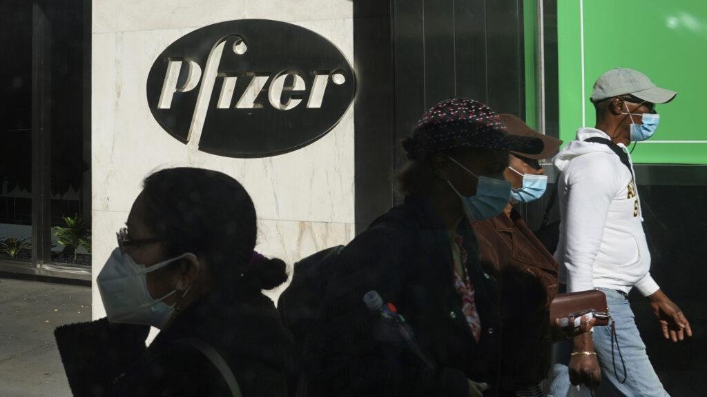 Pedestrians walk past Pfizer
