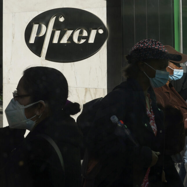 Pedestrians walk past Pfizer