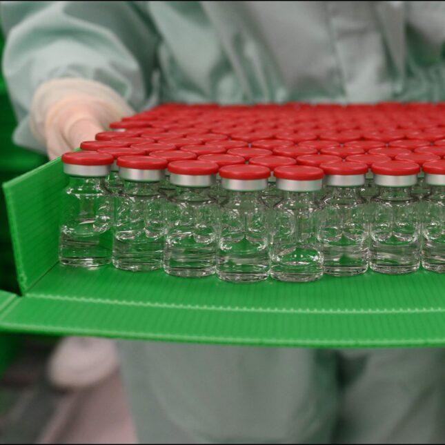 lab tech holding vials adaptive trials