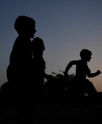 silhouetted children running
